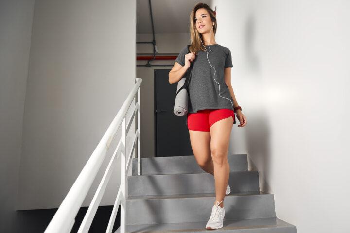 Roupas de Academia: mulher em uma escada com bolsa no braço.