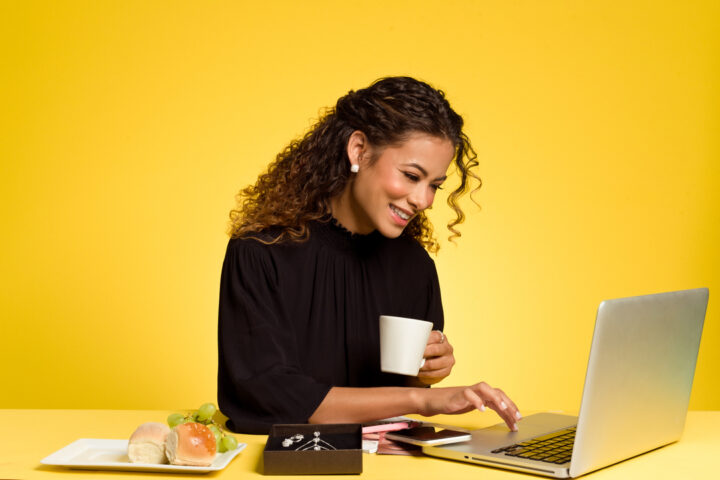 Como fidelizar cliente: mulher de blusa preta e cabelos encaracolados, segurando uma xícara e mexendo em um notebook.
