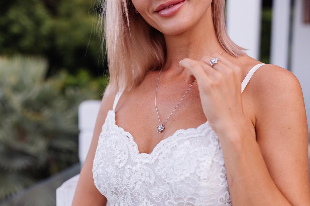 mulher vestida de branco com colar e joia no dedo para representar a diferença entre joia e semijoia